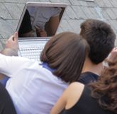 blanc d'isolement de vue arrière le groupe d'amis des étudiants avec un ordinateur portable Photo stock
