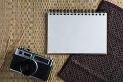 Blanc de carnet sur un plancher en bois avec un appareil-photo de film Photo stock