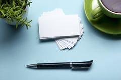 Blanc de carte de visite professionnelle de visite au-dessus de tasse de café et stylo à la table de bureau Maquette de marquage  Images stock