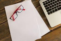 Blanc de livre blanc sur le bureau en bois de table avec des lunettes Photos libres de droits