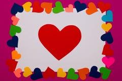 Blanc blanc de papier avec le coeur rouge là-dessus et avec la frontière des coeurs multicolores autour sur le fond rose Photo stock