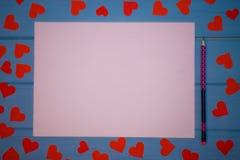 Blanc blanc de papier avec le stylo et de coeurs rouges autour sur le fond en bois bleu Images stock