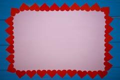 Blanc blanc de papier dans le cadre des coeurs rouges sur le fond en bois bleu Images libres de droits