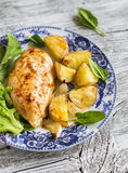 Blanc de poulet cuit au four avec des pommes de terre et des oignons d'un plat de vintage Photos stock
