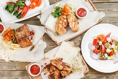 Blanc de poulet et ailes grillés Servir sur un conseil en bois sur une table rustique Menu de rôtisserie, une série de Image stock