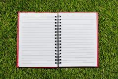 blanc de spirale de papier de cahier d'isolement par blanc de fond carnet de notes à spirale de papier sur l'herbe Photos stock