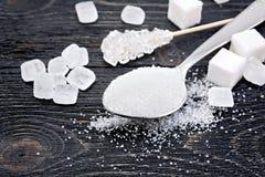 Blanc de sucre dans la cuillère sur le conseil noir Image stock