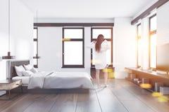 Blanc et chambre à coucher de brique intérieure, vue de côté, femme Photographie stock libre de droits