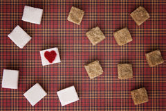 Blanc et cubes en sucre roux avec un coeur rouge sur l'un d'entre eux Vue supérieure Concept doux unhealty de dépendance de régim Image stock