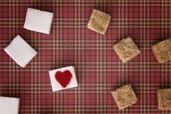 Blanc et cubes en sucre roux avec un coeur rouge sur l'un d'entre eux Vue supérieure Concept doux unhealty de dépendance de régim Photo stock