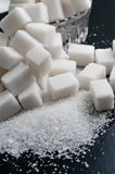 Blanc granulé et sucre raffiné sur la surface noire, plan rapproché photo libre de droits