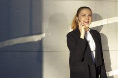 blanc parlant de téléphone d'isolement par femme d'affaires de fond Photographie stock