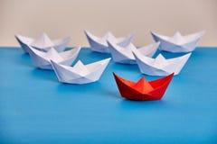 Blanc principal de bateau de papier rouge lumineux ceux basé sur le bleu sur le fond léger Image stock