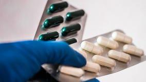 Blanche, vert, rose, la pilule orange de capsules s'est renvers?e du conteneur en plastique blanc de bouteille concept global de  images libres de droits