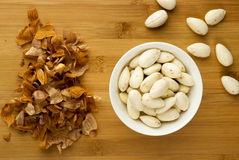 Blanched almonds in a bowl next to almond peels Stock Photography