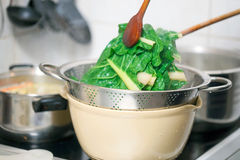 Blanching hot chard using kitchenware Royalty Free Stock Photo