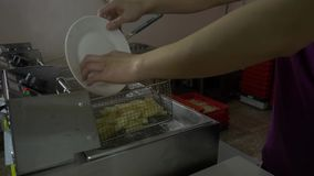 Blanching potatoes. Blanching potatoes before frying. 4K Blanching potatoes. A man puts the sliced potatoes into a deep fryer for blanching stock video footage