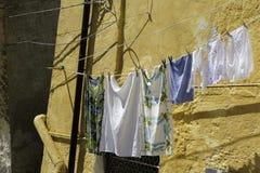 Blanchisserie accrochant au soleil sur un mur jaune de fond Photos stock