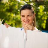 Blanchisserie accrochante de jeune femme extérieure photographie stock libre de droits