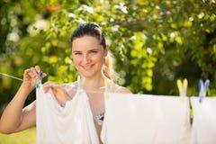 Blanchisserie accrochante de jeune femme extérieure photos libres de droits