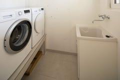 Blanchisserie avec la machine à laver, le dessiccateur et l'évier photographie stock libre de droits