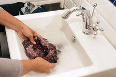 Blanchisserie de lavage à la main dans un évier photographie stock