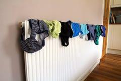 Blanchisserie ou séchage de lavage sur un radiateur domestique photos stock