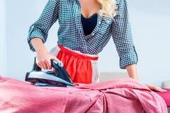 Blanchisserie repassante de femme au foyer image stock