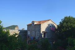 Blanchisserie traînant pour sécher sur une maison en pierre entourée par des arbres photos libres de droits