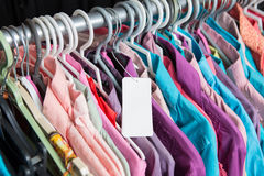 Blanck pricw label on clothes hang on a shelf in a fashion store Stock Image