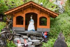 Blanco como la nieve y enanos en un jardín de una casa Imagen de archivo libre de regalías