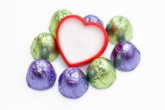 Blanco con un corazón rojo alrededor y algunos chocolates en el empaquetado verde y púrpura en el fondo blanco Fotos de archivo libres de regalías