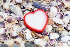 Blanco con un corazón rojo en un fondo de conchas marinas Foto de archivo