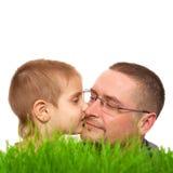 Blanco de la hierba verde del día de padre del beso del niño del padre Imagen de archivo libre de regalías