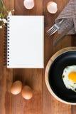 Blanco del cuaderno en un piso de madera con el huevo foto de archivo libre de regalías