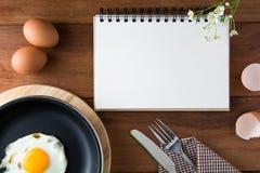 Blanco del cuaderno en un piso de madera con el huevo fotos de archivo libres de regalías