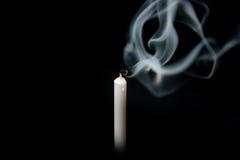 Blanco extinguido de la vela con el humo, aislado sobre negro Foto de archivo