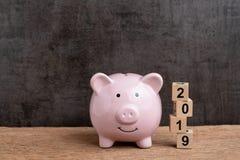 Blanco financiera del año 2019, concepto de las metas del presupuesto, de la inversión o de negocio, hucha rosada y pila de edifi fotografía de archivo