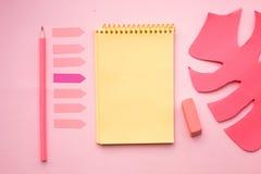 Blanco pagina van verticaal spiraalvormig notastootkussen met kleurpotlood, gom en kunstmatig blad op roze achtergrond stock afbeelding