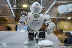 Blanco plástico de Ubtech del abejón del robot del metal con las cámaras de vídeo para los ojos que se sientan en el podio Imagen de archivo libre de regalías