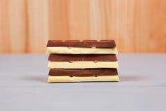 Blanco y barras del chocolate con leche en la madera natural y gris Fotos de archivo