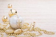 Blanco y bola de la Navidad del oro en fondo iluminado Fotografía de archivo libre de regalías