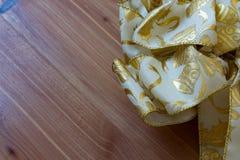 Blanco y cinta de la Navidad del oro contra un fondo de madera diagonal del grano Imágenes de archivo libres de regalías
