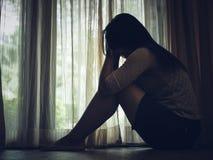 Blanco y negro de mujer triste abrace su rodilla y llore Fotos de archivo