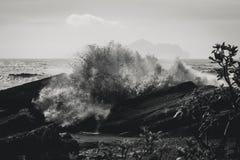 Blanco y negro de un tifón que salpica sobre una roca en la costa de Yilan, Taiwán foto de archivo