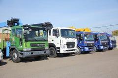 Blancs, bleu, les camions à plat de vert avec le bras de grue est dans le parking - Russie, Moscou, le 30 août 2016 Photos stock