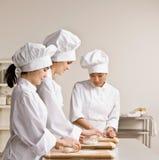 Blancs de collègues de chef malaxant la pâte dans la cuisine photo stock