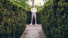 Bland de beautifully kantjusterade buskarna i parkera, en ung man i en vit skjorta, byxa, stilfull hängslen och flugan arkivfilmer
