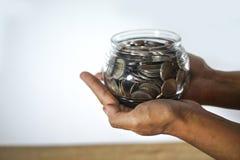 Blanda mynt och kärna ur i klar flaska på vit bakgrund, begrepp för tillväxt för affärsinvestering Arkivfoto