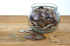 Blanda mynt och kärna ur i klar flaska på vit bakgrund, begrepp för tillväxt för affärsinvestering Royaltyfria Foton